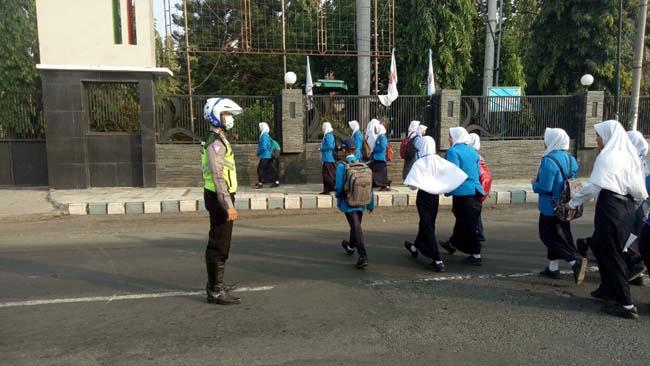 Beberapa pelajar menyeberang Tampak dikawal Polisi. (im)