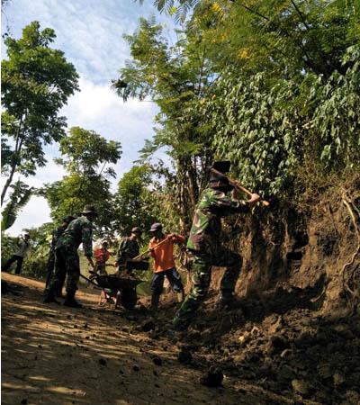 KARYA BAKTI: Anggota Koramil 34 Junrejo dibantu pihak Perhutani dan masyarakat saat melakukan pelebaran jalan menuju tempat wisata air terjun Cuban Putri