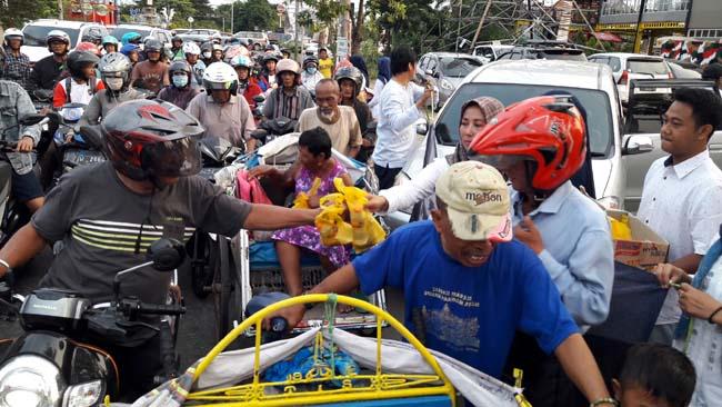 TAKJIL - Puluhan anggota IKA Smanivda membagikan 1.000 paket takjil kepada ratusan pengguna jalan di JL Ponti, Sidoarjo, Sabtu (18/05/2019) petang
