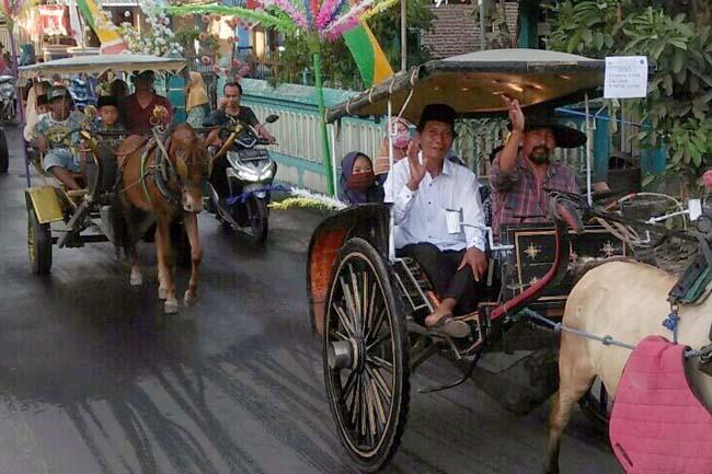 Kepala Desa Grinting, A. Fadil naik delman besama peserta sunatan masal. (par)