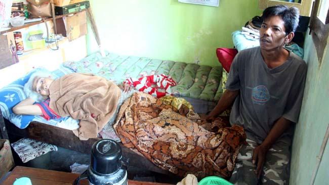 PRIHATIN : Subianah (90) yang hanya bisa berbaring di tempat tidur yang ditemani putranya, Choirul Anam (49) yang juga berharap mendapatkan bantuan dari Pemerintah. (gim)